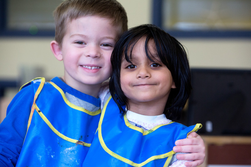 Two young children in painting aprons smiling at the camera