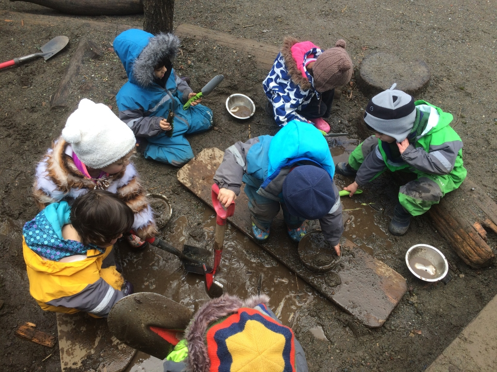 A group of small children digging and playing in muddy sand outdoors