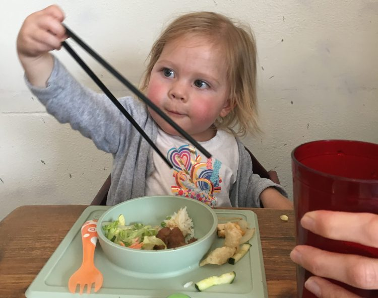 little girl using chopsticks